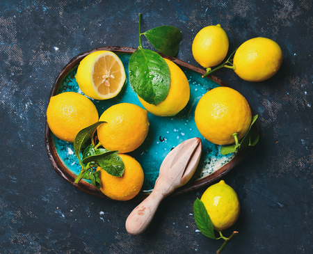 plywood: Freshly picked lemons with leaves in blue ceramic plate over dark blue shabby background, top view