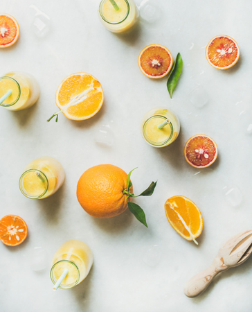Healthy yellow smoothie with citrus fruit, ginger and ice in bottles over light marble table background, top view. Clean eating, vegan, vegetarian, detox, dieting, weight loss food concept