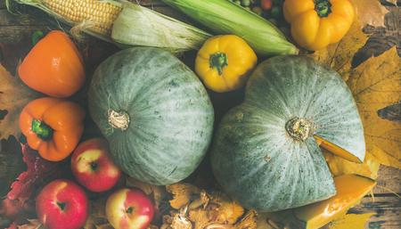 木製のテーブル背景、平面図上秋彩り野菜の品揃え。秋の食品成分背景、パターンやテクスチャ