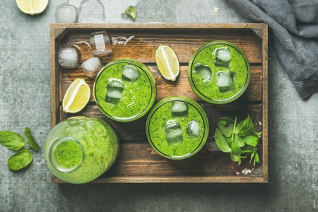 Fresh green smoothie in bottle and glasses with ice cubes, mint and lime in wooden tray over grey concrete background, top view. Clean eating, detox, vegetarian, weight loss, raw, healthy food concept