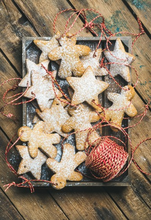 Christmas gingerbread star and angel shaped cookies with sugar powder and decoration rope in wooden tray over rustic background, top view, vertical composition