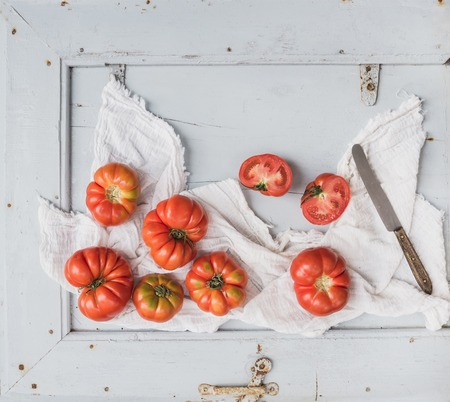 Fresh ripe hairloom tomatoes in rustuc blue wooden tray, top view, copy space