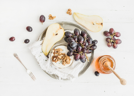 Camembert cheese with grape, walnuts, pear and honey on vintage metal plate over white rustic wood backdrop, top view