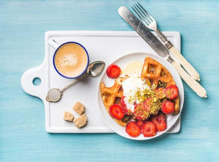 Breakfast set. Warm homemade belgium waffles with whipped cream, strawberry, maple syrup and crushed pistachios, cup of espresso and cubes of brown sugar on white ceramic board over blue painted wooden background, top view