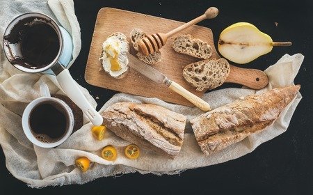 Breakfast set. Cerve pot of coffee, a cup on a kitchen towel, kumquats, pears, baguette slices with butter cream and honey on a rustic wooden board over a black backdrop. Top view