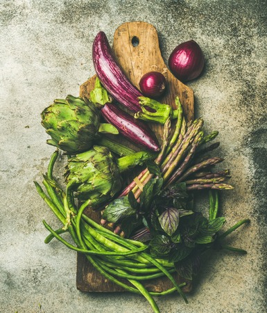 Flat-lay of green and purple vegetables on board over grey background, top view. Local produce for healthy cooking. Eggplans, beans, kale, asparagus, onions, artichoke, basil. Clean eating Stock fotó - 88932227
