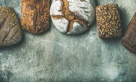Various bread selection flat-lay. Top view of Rye, wheat and multigrain rustic bread loaves over grey background, copy space, horizontal composition Stock Photo