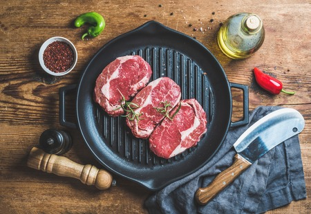 Ingredients for cooking Rib eye roast beef steak on black iron grilling pan over wooden background, top view