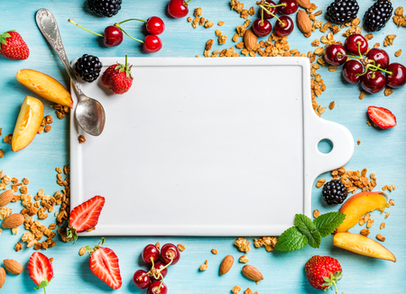 Healthy breakfast ingredients. Oat granola, fruit, berries and mint on blue background with white ceramic board in center, top view, copy space Stock Photo