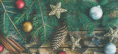 Christmas or New Year holiday flat-lay , top view. Fir tree branches, pine cones, cinnamon, colorful evening balls and baking molds over wooden background