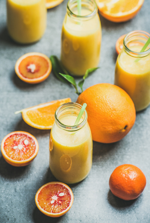 Healthy yellow smoothie with citrus fruit and ginger in bottle over grey concrete background, selective focus. Clean eating, dieting, weight loss, vegetarian, vegan food concept