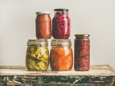 Autumn seasonal pickled or fermented colorful vegetables in glass jars over vintage kitchen drawer, white wall background, copy space. Fall home food preserving or canning Stock fotó