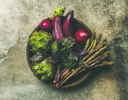 Flat-lay of green and purple vegetables on plate over grey background, top view. Local produce for healthy cooking. Eggplans, beans, kale, asparagus, onions, artichoke, basil. Clean eating