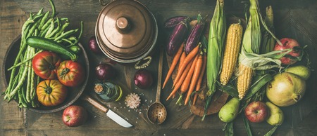 Fall cooking background. Autumn ingredients for Thanksgiving day dinner preparation. Flat-lay of green beans, corn cobs, carrot, tomatoes, eggplant, fruits over wooden table, top view Stock Photo