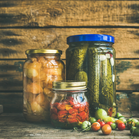 Autumn seasonal pickled vegetables and fruit in glass jars, rustic wooden barn wall background. Fall preserved vegetarian food concept, copy space, square crop