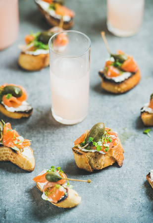Crostini with smoked salmon, pesto sauce, watercress and capers and pink grapefruit cocktails in glass over grey background, selective focus. Party, catering or fingerfood concept