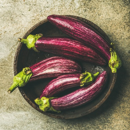 Flat-lay of fresh raw Fall harvest purple eggplants or aubergines in wooden bowl over concrete stone background
