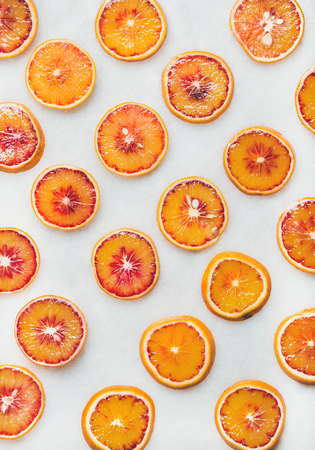 Natural fruit pattern concept. Fresh juicy blood orange slices over light marble table background, top view