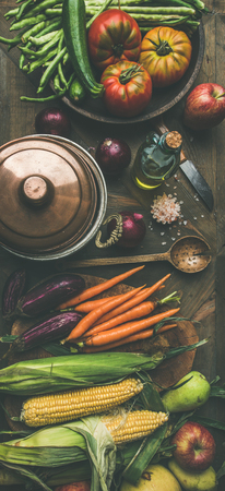Fall cooking background. Autumn ingredients for Thanksgiving day dinner preparation. Flat-lay of green beans, corn cobs, carrot, tomatoes, eggplant, pears, apples over wooden table, top view