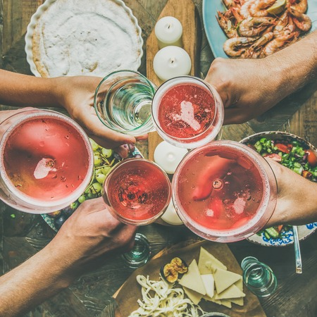 Holiday celebration table setting with food snacks. Flat-lay of friends hands eating and drinking together. Top view of people having party, gathering, celebrating with rose champaign, square crop Stock Photo