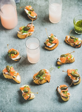Crostini with smoked salmon, pesto sauce, watercress and capers and pink grapefruit cocktails over grey background. Party, catering or fingerfood concept Stock Photo