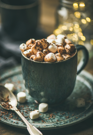 Winter warming sweet drink hot chocolate with marshmallows and cocoa in mug with Christmas holiday lights behind, selective focus