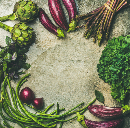 Flat-lay of green and purple raw vegetables over grey background, top view, copy space, food frame. Local produce for healthy cooking. Eggplans, beans, kale, asparagus, artichoke, basil. Clean eating Stock Photo