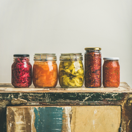 Autumn seasonal pickled or fermented vegetables in jars placed in line over vintage rustic kitchen drawer, white wall background, copy space, square crop. Fall home food preserving or canning