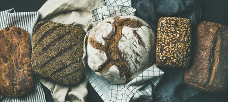 Various bread selection flat-lay. Top view of Rye, wheat and multigrain rustic bread loaves over black background, wide composition 写真素材