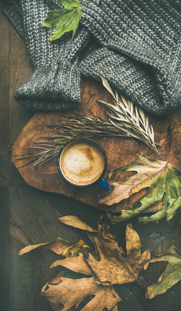 Autumn or Fall morning coffee concept. Flat-lay of knitted woolen grey sweater, wooden tray, mug of coffee and yellow fallen leaves over dark rustic table background, top view, vertical composition