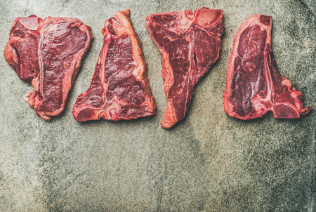 Flat-lay of fresh raw beef meat steak cuts over grey concrete background, top view, copy space. Porterhouse, t-bone and rib-eye steaks. Butcher s shop or cooking meat dinner concept