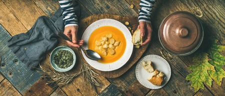 Flat-lay of female hands eating Fall warming pumpkin cream soup with croutons and seeds over rustic wooden table background, top view. Autumn vegetarian, vegan, healthy comfort food eating concept
