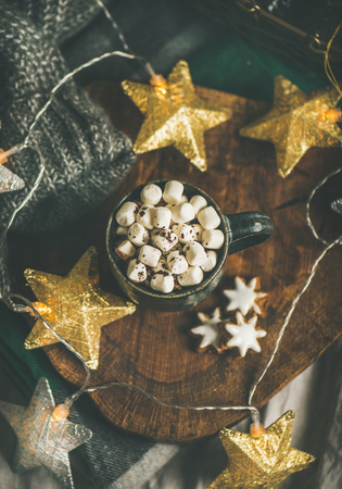 Christmas or New Year winter hot chocolate with marshmallows and gingerbread cookies over rustic wooden board served with holiday light garland and grey sweater, selective focus, top view Stock Photo