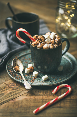 Winter warming sweet drink hot chocolate with marshmallows and cocoa in mug with Christmas holiday candy cane on wooden background, selective focus, copy space
