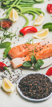 Raw uncooked salmon fish fillet steaks with vegetables, greens, rice and spices over grey marble background. Clean eating, alkaline diet, dieting, power boosting, vegetarian, weight loss concept Stock Photo