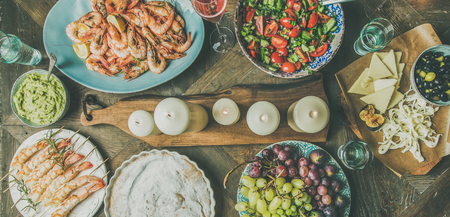 Holiday celebration table setting with snacks. Flat-lay of salad, shrimps, olive, grape, homemade cake over wooden background, top view, wide composition 写真素材