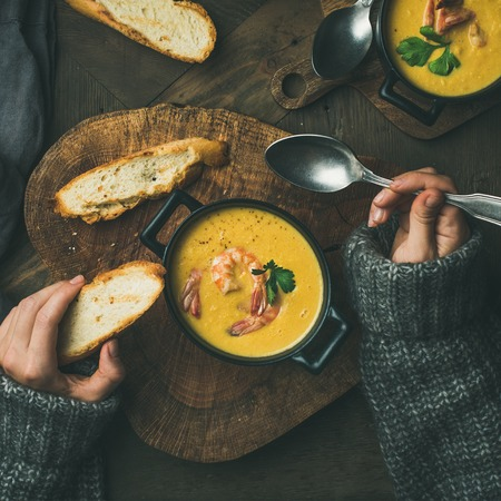Woman in sweater eating corn creamy soup with shrimps in individual pot, top view, square crop. Woman s hand with spoon and bread. Flat-lay of rustic table. Slow food, winter warming food concept Stock Photo
