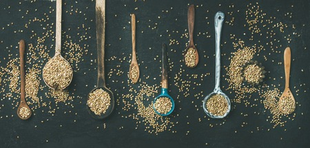 Flat-lay of various old vintage kitchen spoons full of green uncooked buckwheat grains over black stone background, top view, copy space, wide composition. Rustic cooking concept