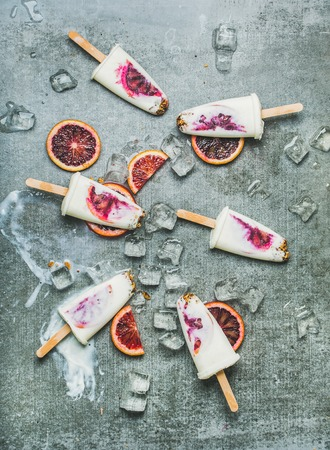 Healthy summer dessert. Blood orange, yogurt and granola  on ice cubes over grey concrete background, top view, vertical composition. Clean eating, dieting, weight loss concept