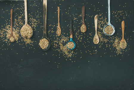 Flat-lay of various old vintage kitchen spoons and green buckwheat grains over black stone background, top view, copy space. Rustic cooking concept