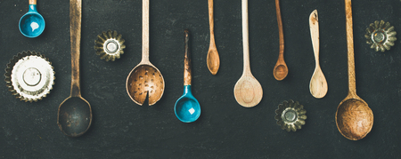 Flat-lay of various old vintage kitchen spoons and baking tin molds over black stone background, top view, copy space, wide composition. Rustic cooking concept