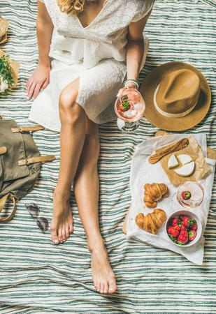 프랑스 스타일 로맨틱 피크닉 설정입니다. 와인, 딸기, 크로 상, 브리 치즈, 선글라스, 밀 짚 모자, 모란 꽃 담요, 상위 뷰의 유리 드레스와 여자. 야외