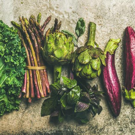 Flat-lay of green and purple fresh vegetables over concrete background, top view, square crop. Local produce for healthy cooking. Eggplans, green beans, kale, asparagus, artichoke, basil. Clean eating