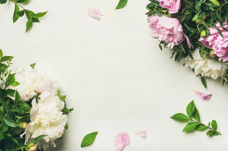 Disposition florale de printemps avec des fleurs. Pose plate de pivoines roses et blanches tendres sur fond blanc, vue de dessus, espace copie. Carte de voeux ou invitation de mariage Banque d'images - 94342755