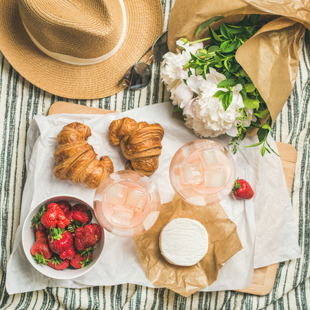 French style summer picnic setting. Flat-lay of glasses of rose wine, strawberries, croissants, brie cheese on board, hat, sunglasses, peony flowers, top view, square crop. Outdoor gathering concept Stock Photo