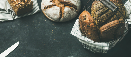 Various bread selection. Rye, wheat and multigrain rustic bread loaves on kitchen towels over grey concrete stone background, copy space