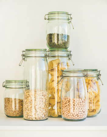 Various raw cereals, grains, beans and pasta for healthy cooking in glass jars on kitchen shelf, white background. Clean eating, vegetarian, vegan, balanced dieting food concept