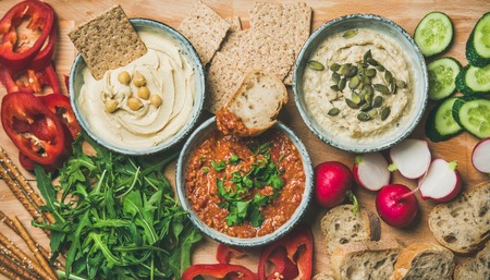 Vegan snack board. Flat-lay of various Vegetarian dips hummus, babaganush and muhammara with crackers, bread and fresh vegetables, wooden background, top view. Clean eating, dieting food concept Stock Photo