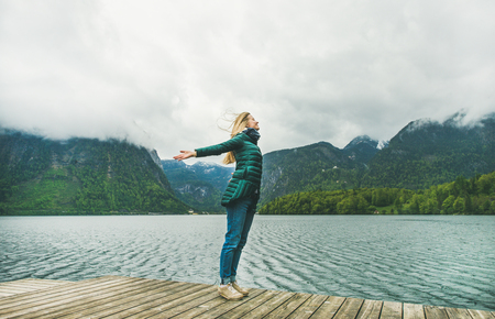 Relaxed female traveller with her arms open, standing at mountain lake coast enjoying the view of the Alps in Austria. Freedom concept