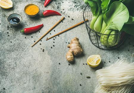 Aziatische keukeningrediënten over grijze concrete achtergrond, exemplaarruimte. Groenten, kruiden, noedels, sauzen voor het koken van Vietnamees, Thais of Chinees eten. Schoon eten, veretarisch voedselconcept